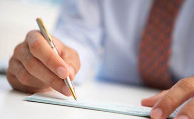 Мужская рука подписывает документ