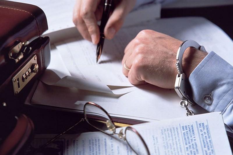 Мужчина в наручниках, подписывающий бумаги