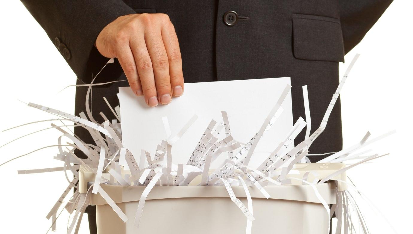 Мужчина выкидывает в коробку бумагу